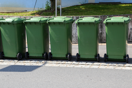 Green garbage cans are on the street.