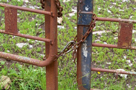 Rusty metal gates tied with metal chain.