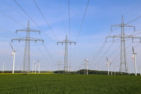 Landscape with high-voltage masts against the blue sky.