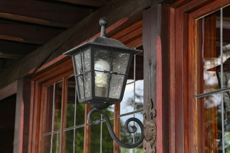 Beautiful lamp on the wall of a wooden house. Imagens