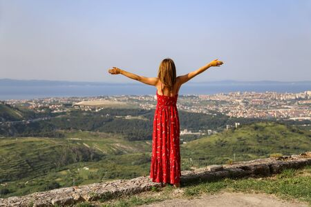 A girl with open arms stands on the edge of a cliff high above the city