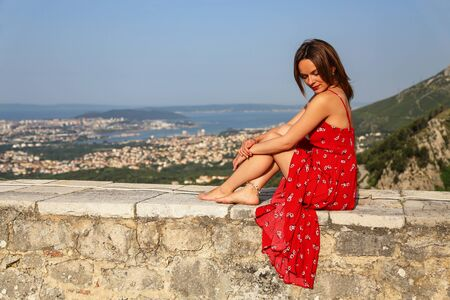 The girl sits on the fortress wall.