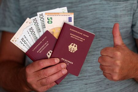 Two new German passports and vacation money in the hands of a man