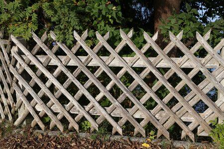 Wooden wattle fence in a garden near a rural house.