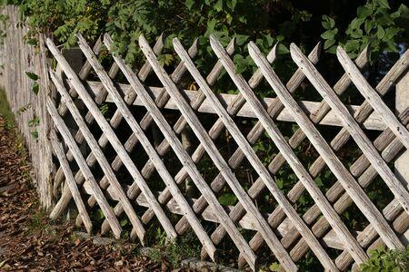 Wooden wattle fence in a garden near a rural house