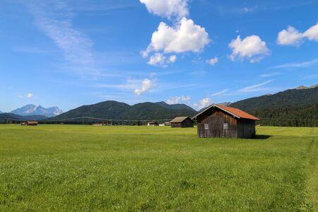 Mountain huts on green meadows in summer in the Alps