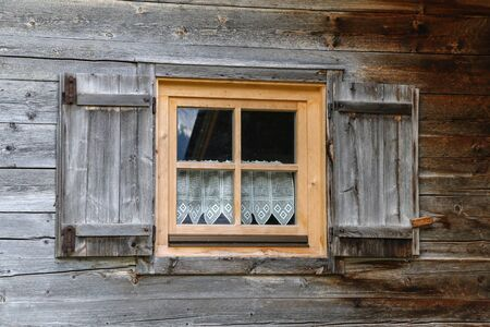 Windows with shutters in a wooden house.