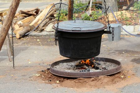 Food is cooked in a cauldron on a fire. Banco de Imagens