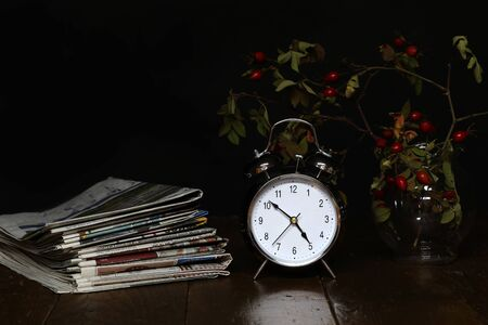 Still life with an alarm clock and old newspapers.