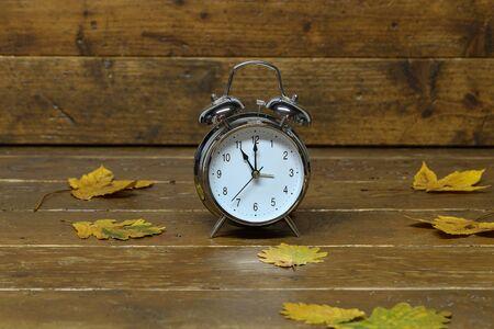 Autumn still life with an old alarm clock.