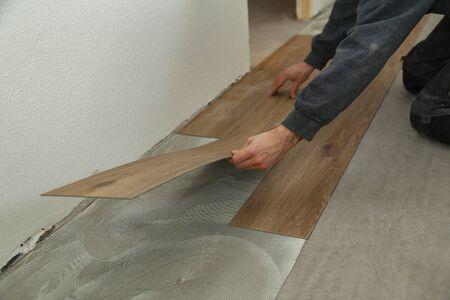 The worker installing new vinyl tile floor.