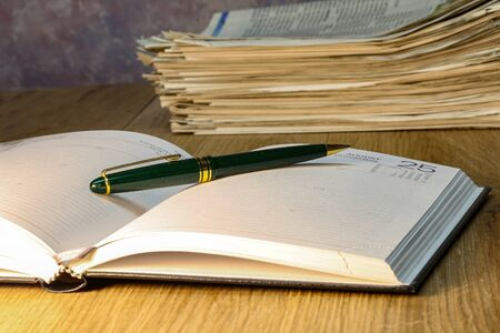 Pen lying on calendar or organizer on desk in office.