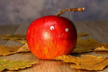 Beautiful red apple with eyes and nose is on the table Reklamní fotografie