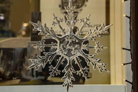 A crystal snowflake hangs in a shop window