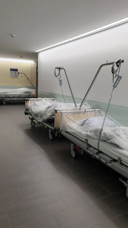 Beds for patients stand in the corridor of the clinic.