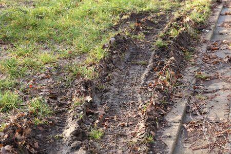 Trace of the tread of a car wheel in autumn mud Фото со стока