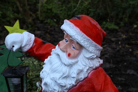 Ceramic Santa Claus holds a New Year lantern in his hand