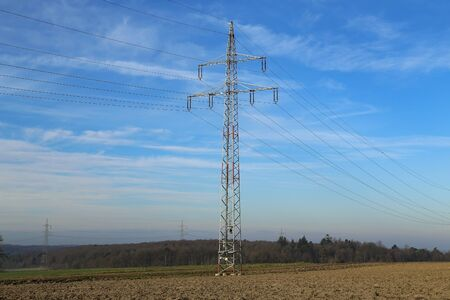 Landscape with electric pylons against the blue sky Фото со стока