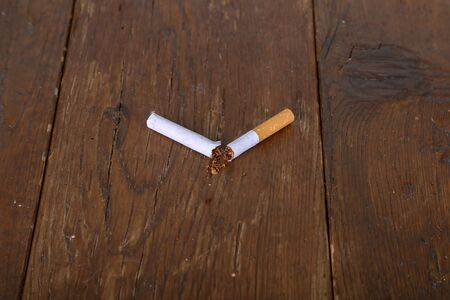 Broken Cigarette with filter lies on a wooden table