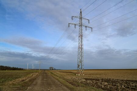 Landscape with high voltage masts against the blue sky