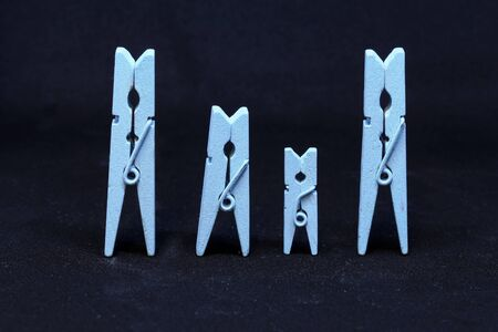 Blue wooden clothespins on a black background