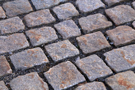 Abstract background of old cobblestone pavement close-up. Standard-Bild