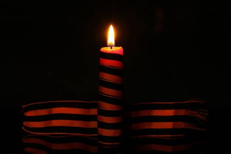 Burning candle of memory wrapped in a George ribbon.