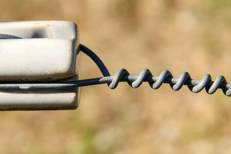 close up of a electrical wire fence around a pasture
