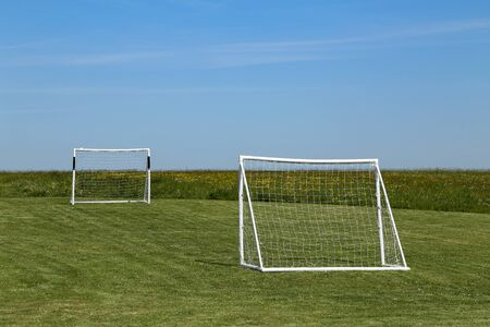 Football goal stand on a green lawn.
