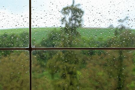 Rainy weather behind wet glass of a house window. Standard-Bild