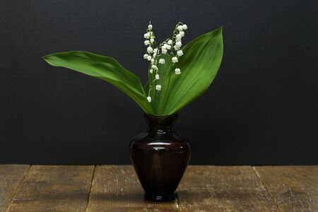 A bouquet of lilies of the valley in a small vase is on the table