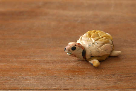 Animals fashioned by children from plasticine - a turtle. Standard-Bild