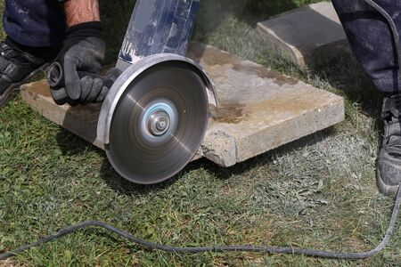 Using an angle grinder which is a handheld power tool to cut bricks at a construction site Banco de Imagens