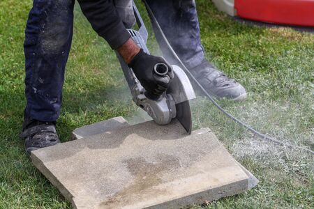 Using an angle grinder which is a handheld power tool to cut bricks at a construction site Standard-Bild