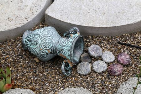 Decorative jug with lying colored pebbles garden decoration. Stock Photo