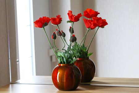 Decorative red poppies stand on a shelf with a mirror.