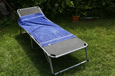 A folding bed is in the garden on the green grass. Stock Photo