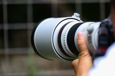 The telephoto lens in the hands of the photographer