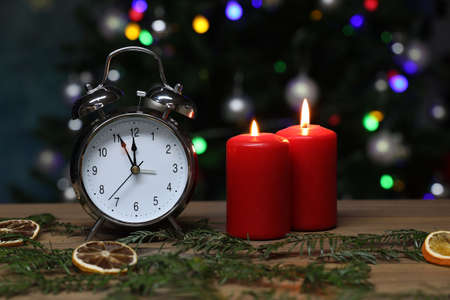 New year composition with alarm clock and burning candles Imagens