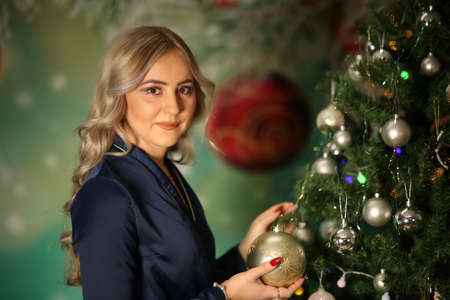 Girl hangs beautiful balls on the Christmas tree