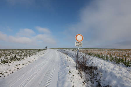 Country road in winter. Text on the sign in German - Agricultural traffic free. Reklamní fotografie