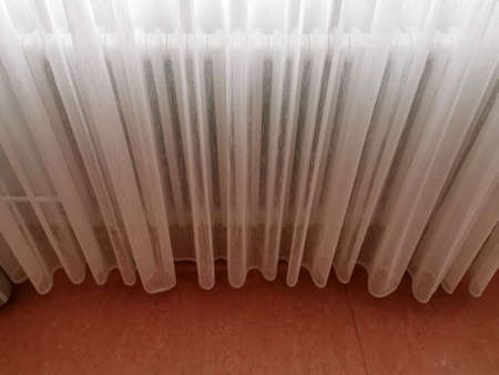 A transparent white curtain covers the radiator