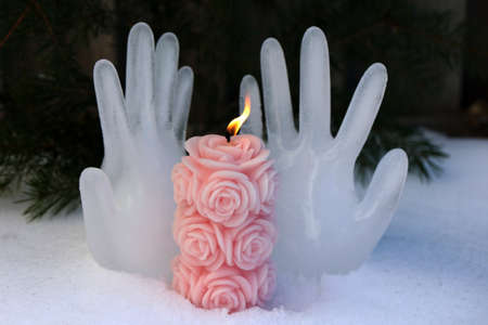 Burning candle on the background of hands made of ice Stock fotó