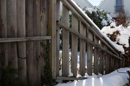 Wooden fence in the garden in winter