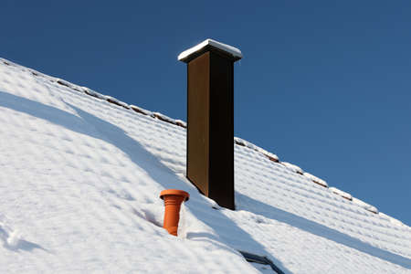 The roof with a chimney is covered with snow in winter Reklamní fotografie