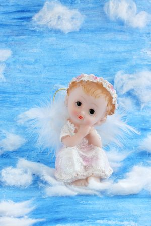 Angel sitting on the white clouds in the sky photo