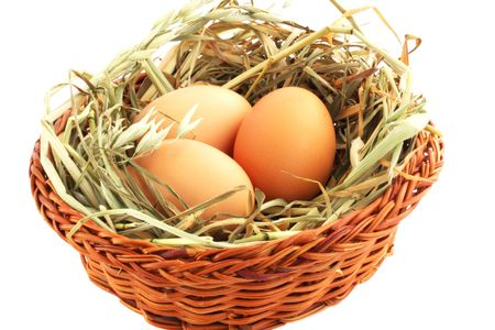 Three eggs in basket with the hay against the white background photo