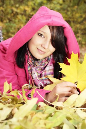 girl at the hood lies on the yellow the foliage photo