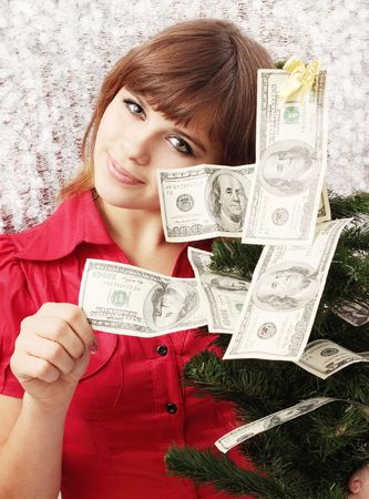 christmas savings: Girl holds Christmas tree decorated with money Stock Photo