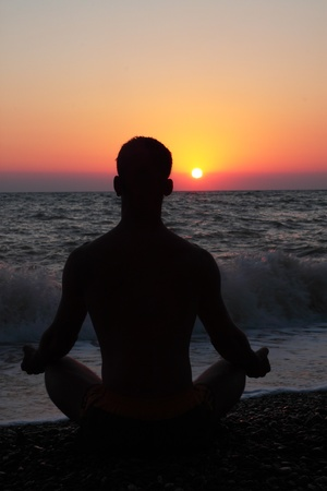 inner peace: Man in the meditation on the shore of the sea